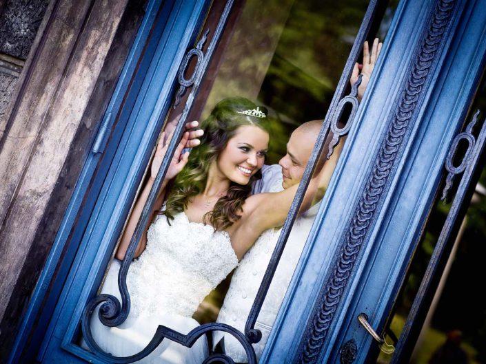 Plener ślubny, Para Młoda pozuje do zdjęć ślubnych za pięknymi przeszklonymi drzwiami Zamku Moszna